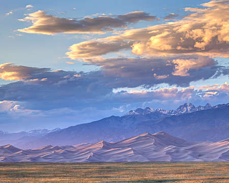 sand dunes: Sun sets on the Gread Sand Dunes backed by snow capped mountains. Stock Photo