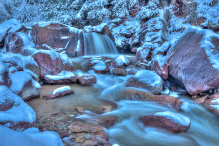 finds: Early morning light finds fresh snow on boulders as water rushes by.
