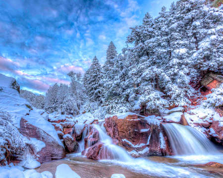 rushes: Cold water rushes over the rocks forming a waterfall round freshly fallen snow. Stock Photo