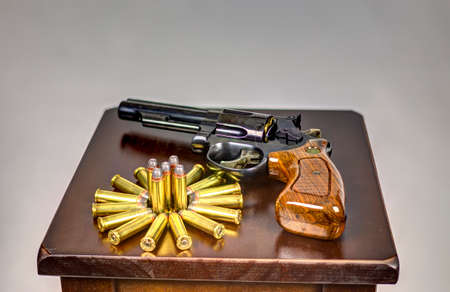 ammo: Revolver laying on a table with ammo arranged