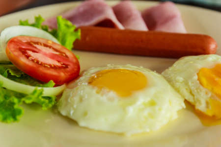 Breakfast with fried eggs, hotdog and fresh vegetable photo