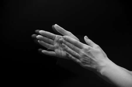 sideview: Female hands clapping on black, side-view
