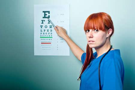 oculista: m�dico oculista femenino examen paciente con una carta de ojo detr�s