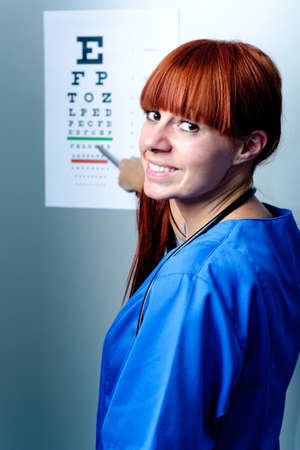 hyperopia: female oculist doctor examining patient with an eye chart behind Stock Photo