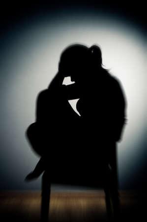 trieste vrouw zitten alleen in een lege kamer