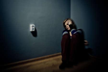 trieste vrouw zit alleen in een lege kamer