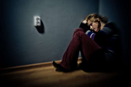 sad woman sitting alone in a empty room Stock Photo - 17802969