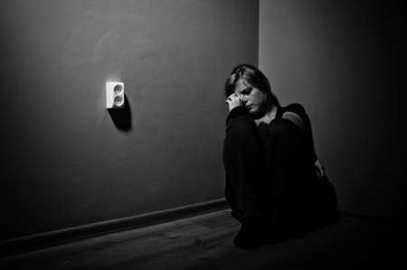 sad woman sitting alone in a empty room - black and white photo