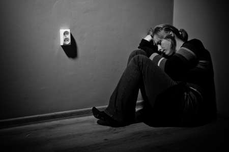 misery: sad woman sitting alone in a empty room - black and white