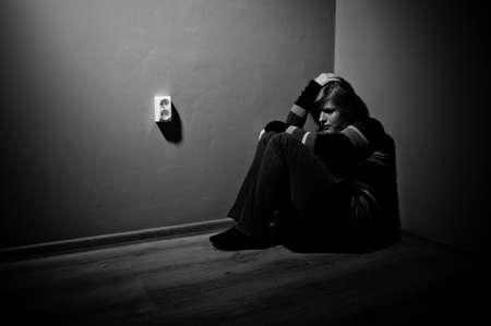 trieste vrouw zitten alleen in een lege kamer - zwart en wit