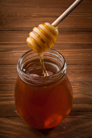 Honey drip in jar on the table Stock Photo