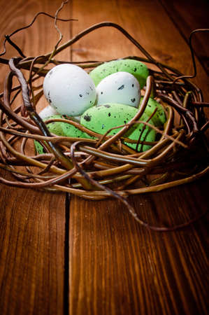 Easter eggs in nest on rustic wooden planks Stock Photo