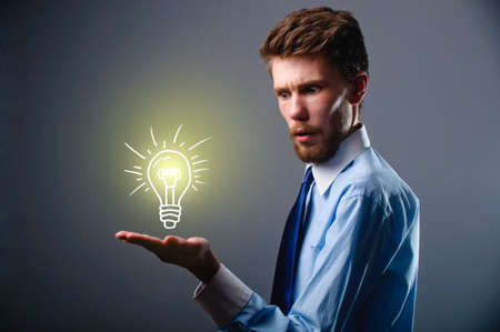 Light bulb in hand business man on blue background photo