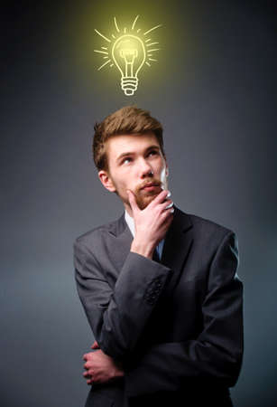 Young businessman with thoughtful expression and light bulb over his head photo