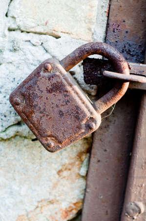 doorlock: very old rusty padlock on the door