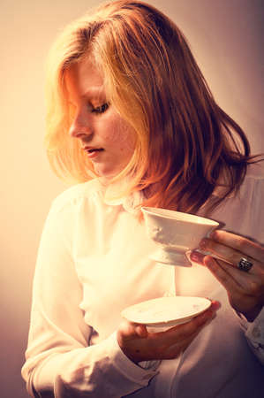 young woman with a cup of coffee or tea - retouching Vintage photo