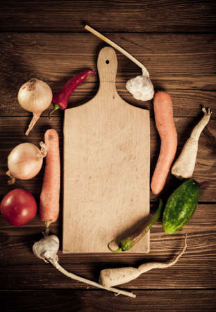Vegetables and spices vintage border and empty cutting board photo