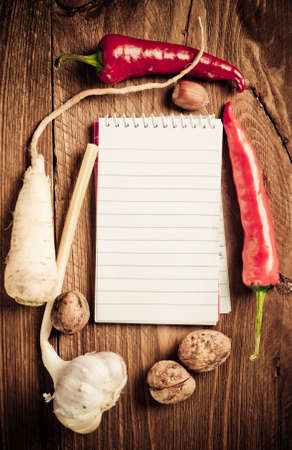 Open notebook with vegetables on the old wooden cutting board photo