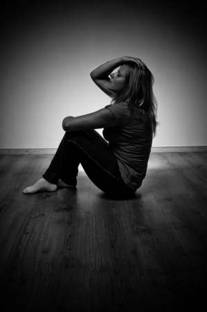 sad woman sitting alone in a empty room photo