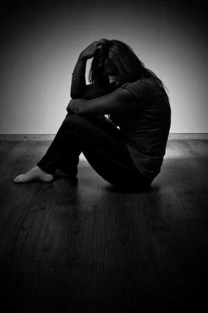 faccia disperata: triste donna seduta da sola in una stanza vuota