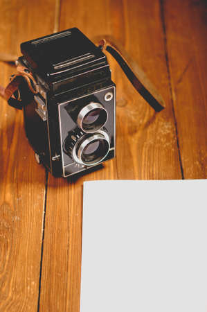 Vintage camera on wooden background with a paper photo