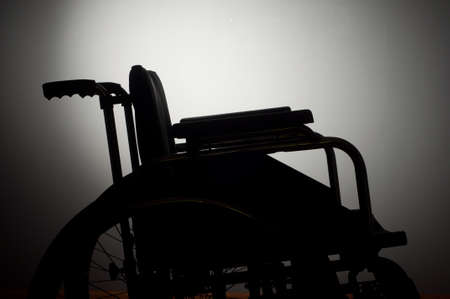 Close-up lege rolstoel op een donkere achtergrond en schaduw Stockfoto