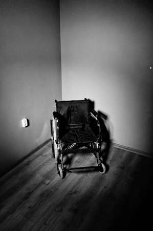 Closeup empty wheelchair on dark background and shadow in empty room photo