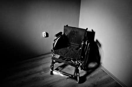 Close-up lege rolstoel op een donkere achtergrond en schaduw in lege ruimte