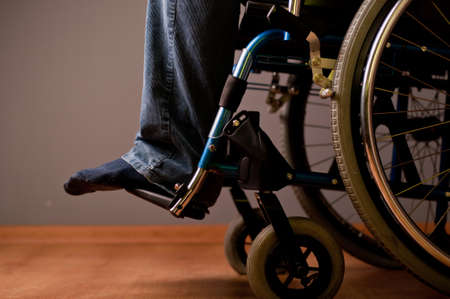 Close-up of male hand on wheel of wheelchair Stock Photo