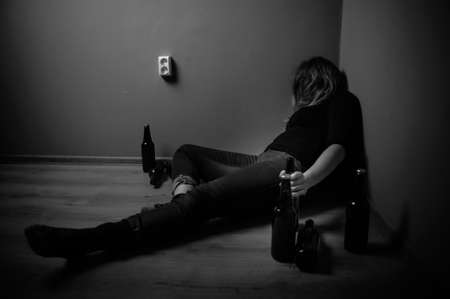 drinking alcohol: sad woman drinking alcohol, black and white Stock Photo