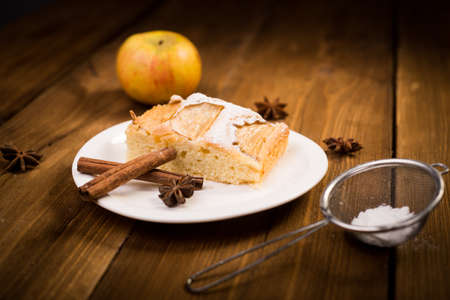 Apple pie on a wooden table. In the background, cinnamon, apple and anise Stock Photo