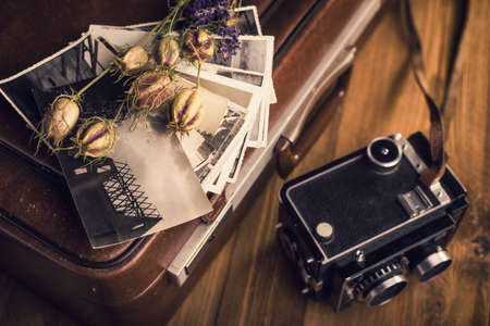 Old photographs, a camera and dried flowers