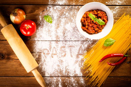 ingredients for spaghetti on a wooden table