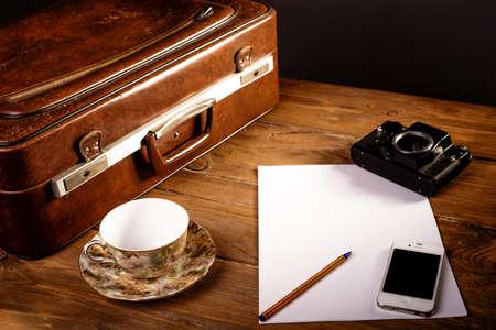 Koffer en oude camera, tablet, telefoon en een kopje koffie. Stockfoto