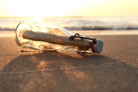 message: message in a bottle on the beach at sunset