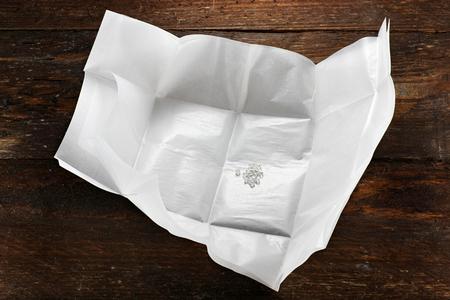 Rohdiamanten in einem traditionellen Diamant Paket auf Holzuntergrund
