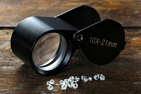 rough diamond: rough diamonds with folding magnifier on wooden background