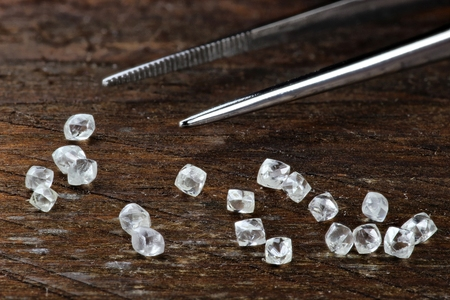 Rough Diamonds with tweezers on wooden background 免版税图像