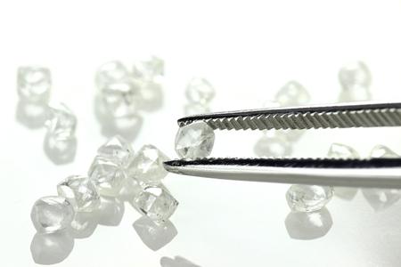 ruwe diamant gehouden door een pincet op een witte achtergrond Stockfoto