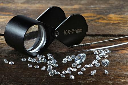 cięte diamenty ze składanym lupy i pinceta na drewnianym tle