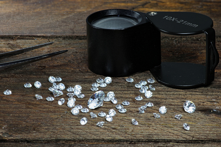 cut diamonds with folding magnifier and tweezers on wooden background