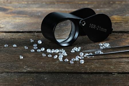 カット ダイヤモンドの木製の背景に折り畳み拡大鏡とピンセット 写真素材