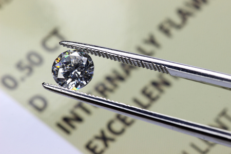 tweezers: Cut Diamond held by tweezers above certificate