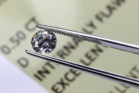 Geslepen diamant in het bezit van een pincet boven certificaat Stockfoto