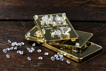 an ounce: gold bullions and diamonds on wooden background