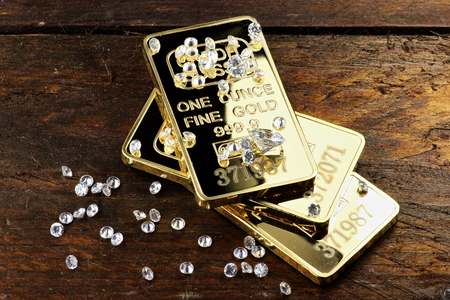 gold bullions and diamonds on wooden background