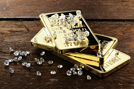 raw gold: gold bullions and diamonds on wooden background