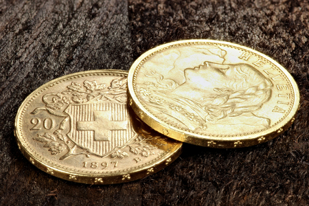 2 Swiss Vreneli gold coins on wooden background