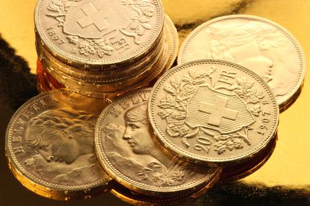 helvetia: Swiss Vreneli gold coins on golden background Stock Photo