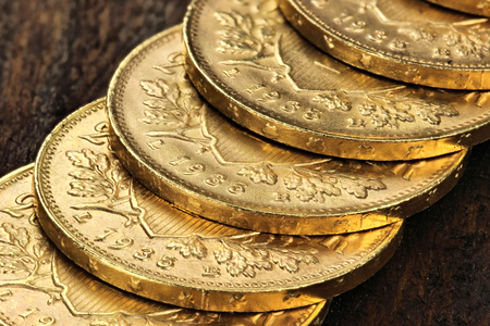 helvetia: Row of Swiss Vreneli gold coins on wooden background